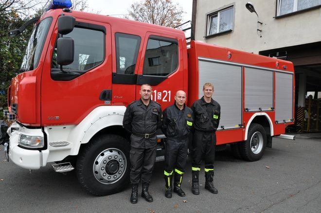W tle nowy wóz PSP. Od lewej Rafał Adamczyk,Andrzej Boehm, Dawid Izworski